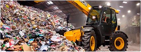 Погрузчик загружает мусор с объекта демонтажа