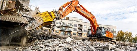 Процесс демонтажа здания экскаватором